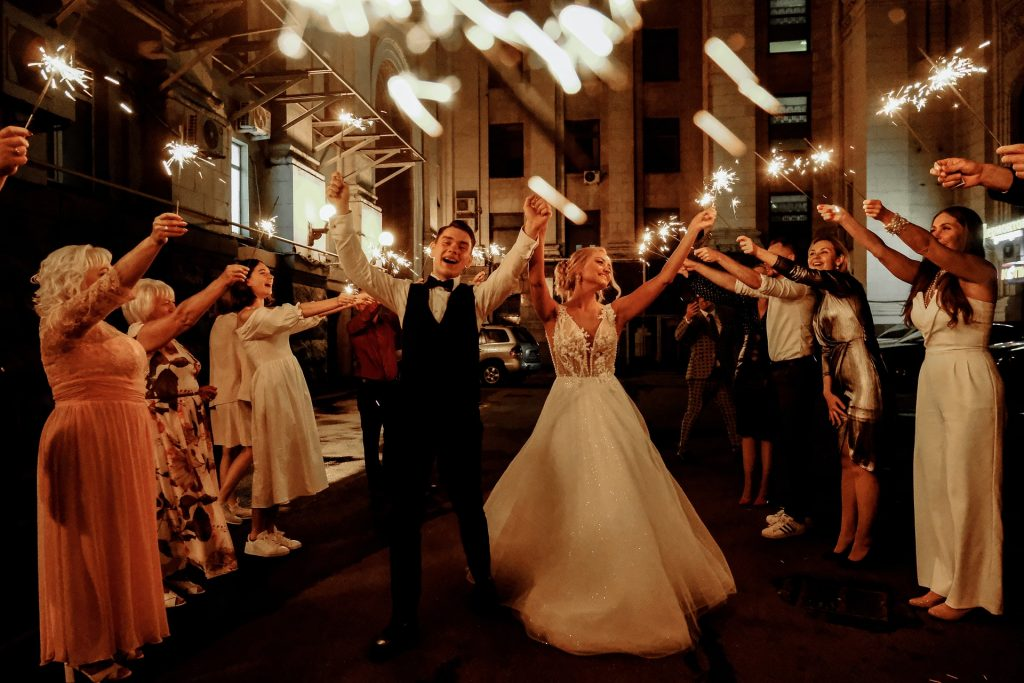 A married couple among guests holding up sparklers.