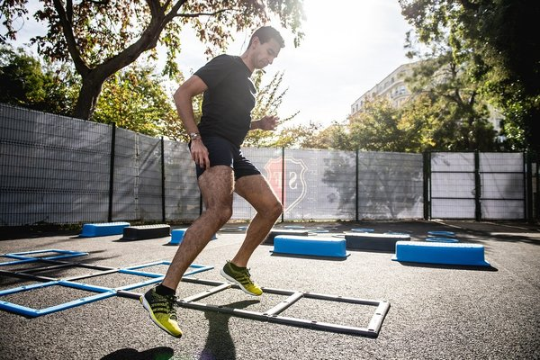 Man jumping over agility ladder outdoors