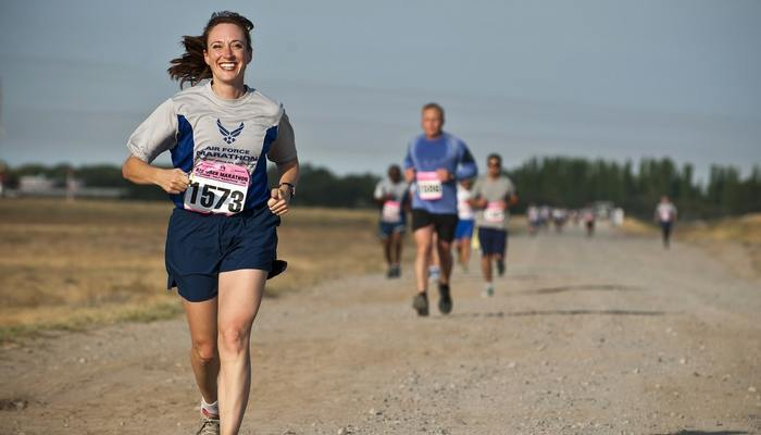 Smiling woman running in a marathon.
